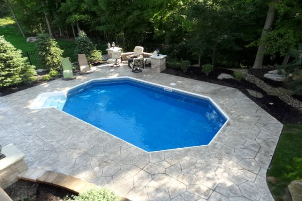 Beautiful hardscaped pool deck patio with inground pool installed by H&M Landscaping.