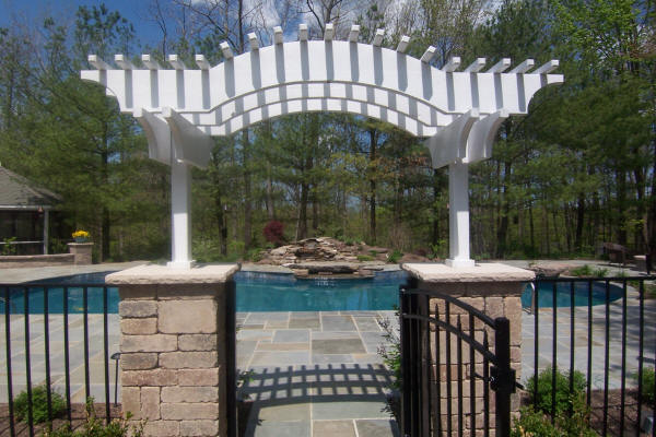 Landscape arbor built on pillars leading to pool area with hardscaped deck and water fall in the background.
