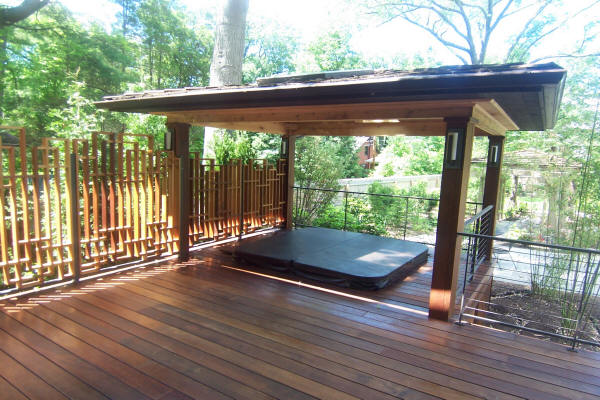 Wooden deck surrounded by privacy fence featuring covered hot tub designed and installed by H&M Landscaping.
