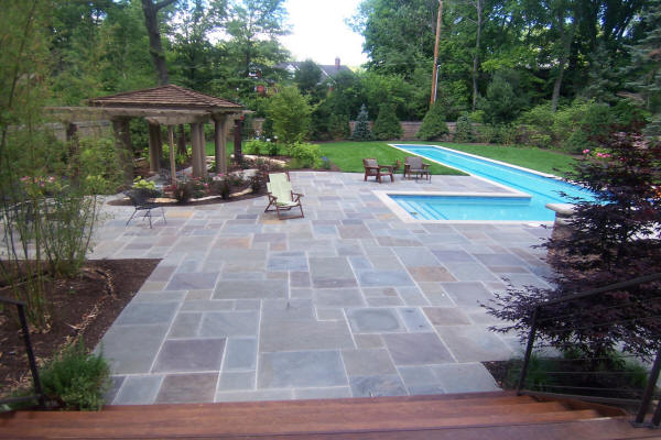 Beautiful hardscaped pool deck with gazebo and pool in the background installed by H&M Landscaping.
