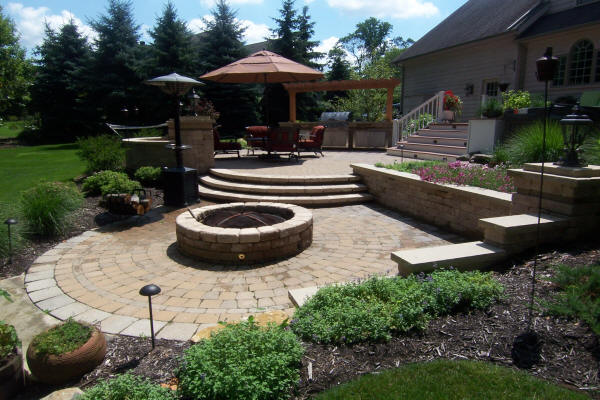 Outdoor patio terrace with outdoor fire pit in the foreground and retaining walls built by H&M Landscaping.