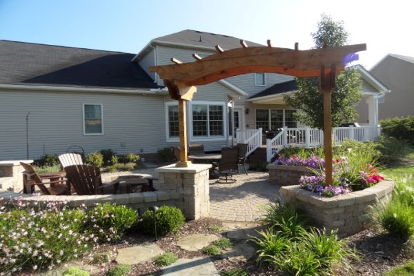 Landscape arbor built on pillars surrounded by landscape plantings installed by H&M Landscaping.