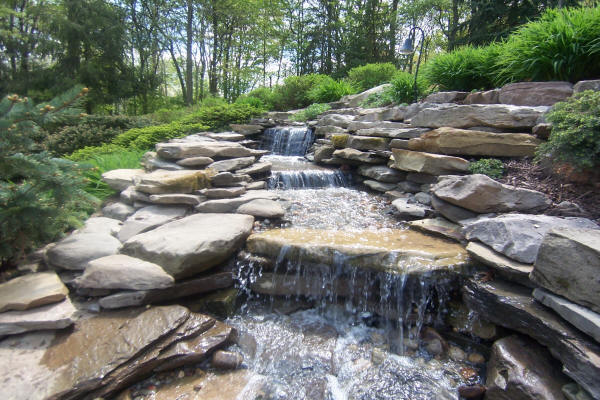 Close up of beautiful landscaped natural stone creek surrounded by landscape plantings installed by H&M Landscaping.