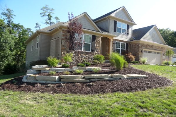 Backyard landscaped bed with natural stone retaining walls built by H&M Landscaping.