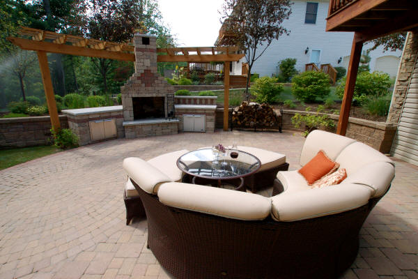Outdoor living room with round brick patio and outdoor fireplace built by H&M Landscaping.