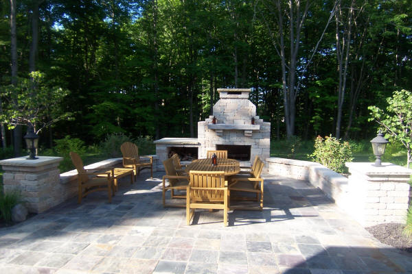 Outdoor patio area featuring wall, pillars and outdoor fireplace in the background constructed by H&M Landscaping.