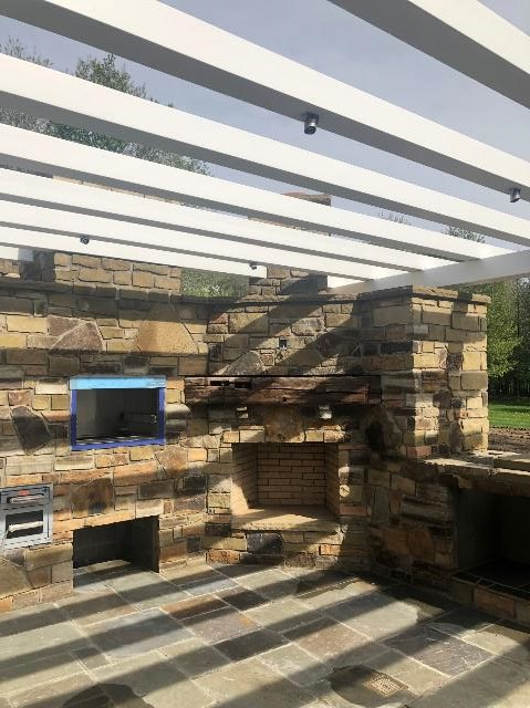 Outdoor Fireplace with Pizza Oven by H&M Landscaping